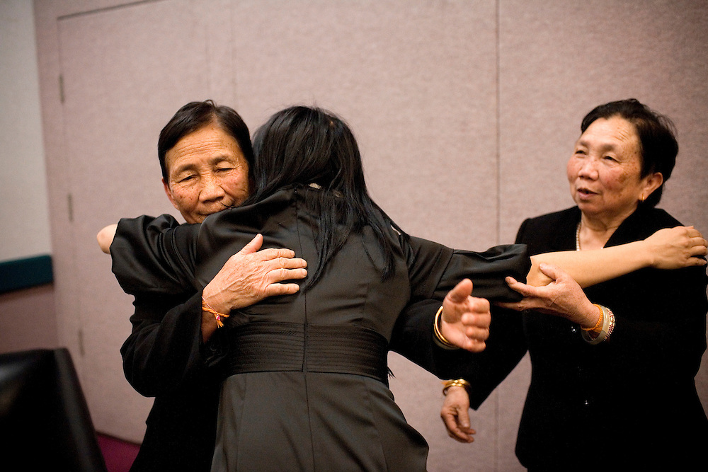 NPR reporter Doualy Xaykaothao hugs her great-aunts, Lee Vang, left, and Chai Vang, right, in Fresno, Ca., on Sunday, Feb. 6, 2011.
