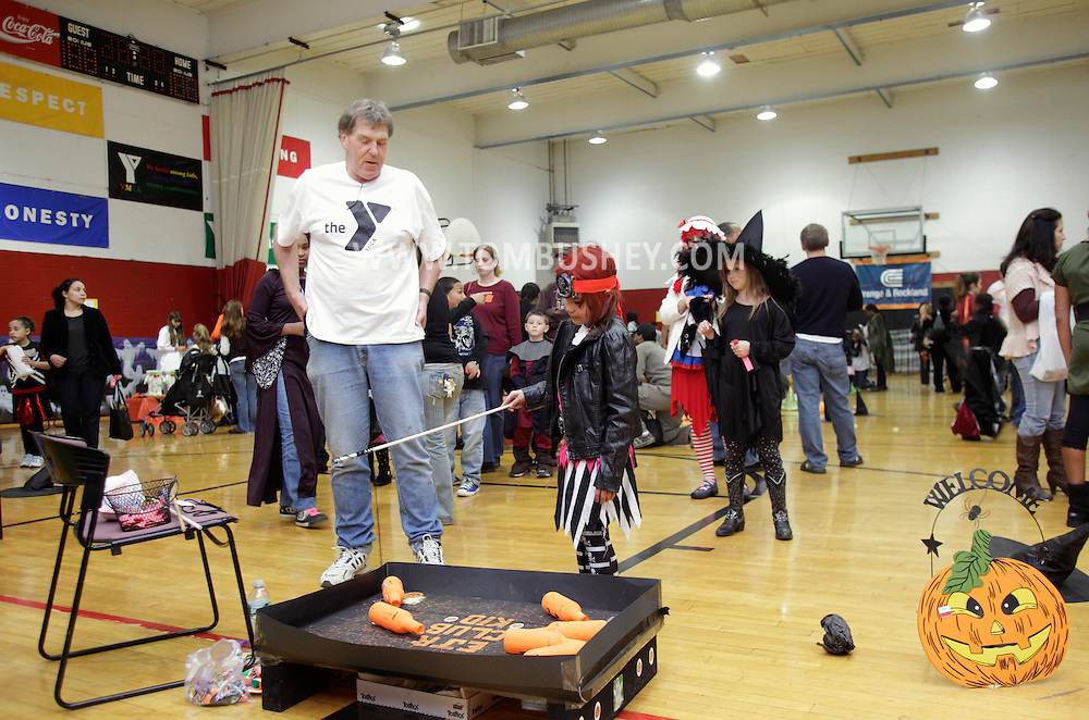Middletown, New York - A girl wearing a costume plays a game during the Family Fall Festival at the Middletown YMCA on Oct. 23, 2010.