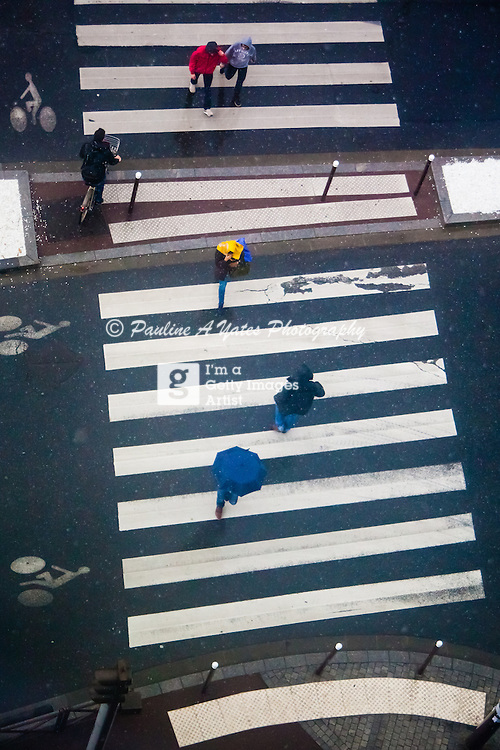 Taken for a Getty Brief - available exclusively on Getty.<br /> <br /> A birds eye view of commuters in the rain crossing a street in Paris.