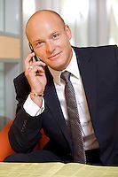 Businessman conversing on mobile phone, portrait