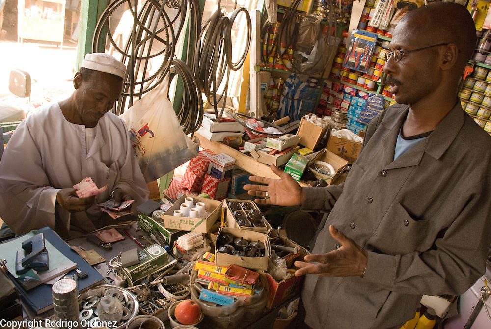 "Trader Mohammed Abdulrahman, from El Muglad (left), gives change to a customer at his hardware store in the market of Abyei. Recent developments in Abyei town are making people settle down. ""No one was thinking of using these materials before."""