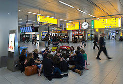Travelers stranded by the ash cloud from a volcanic eruption in Iceland, wait for flights to resume at Schiphol Airport in Amsterdam, the Netherlands, on Tuesday, April 20, 2010. (Photo © Jock Fistick)