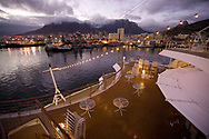 A night view from the stern of a cruise ship, looking towards the harbor and the Victoria and Alfred Waterfront of Cape Town, South Africa.