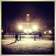 Someone walks across college green during the first hard snowfall of spring semester in January 2013.