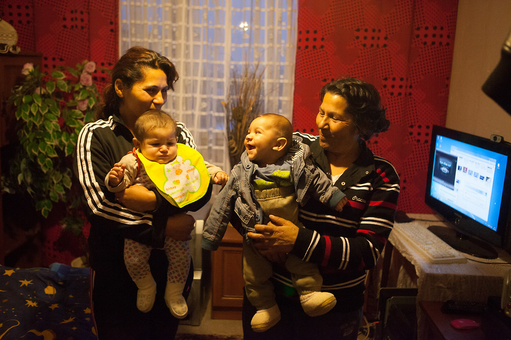 """Milena (left) with her mother Bozena (58) holding their grand and great grand children in their new flat after moving out of the concrete building """"Hrebenova 34-36""""  which was in an appalling condition and demolished in August 2014 by the city of Kosice. The family of Milena, her mother Bozena and their children had been one of the last families living in that building waiting for a compensatory flat which they received a short while later. They belonged among the 5% of inhabitants of that building which had a renting contract, were paying rent and with that the right to get a new flat located at the Lunik IX housing estate."""