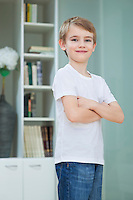 Portrait of little boy in casuals standing with arms crossed at home
