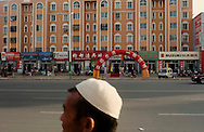 In Kashgar, a Uyghur by a new residential building with a line up of Han Chinese stores. Xinjiang economic development has mainly benefitted Han Chinese.