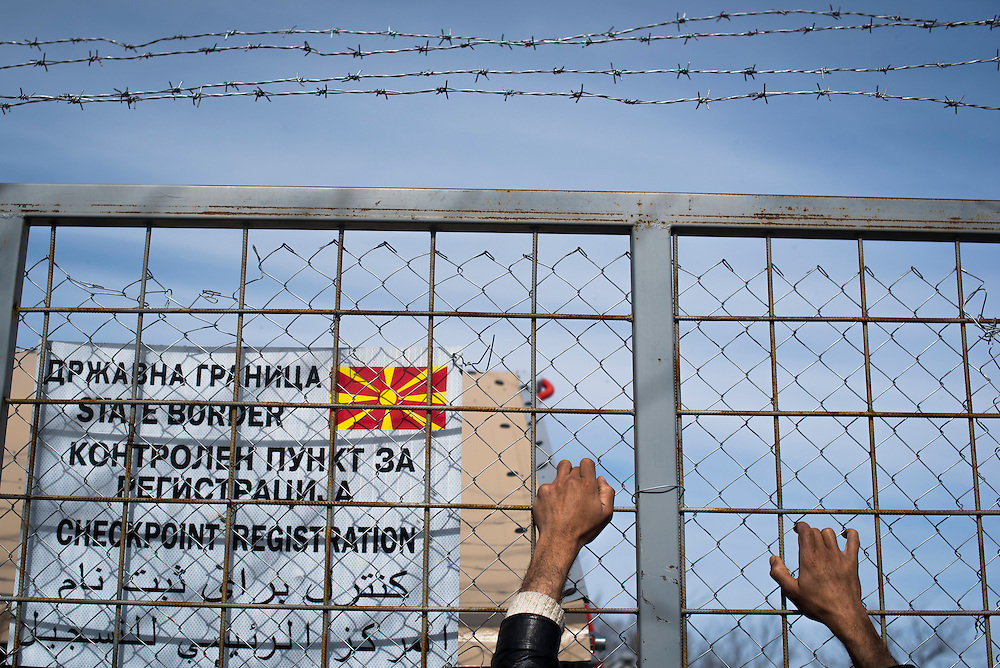 A refugee holds on to a small gate in fence securing the Macedonian (FYROM) border on March 8, 2016 in Idomeni, Greece. No one has been let through the Idomeni crossing since March 6.