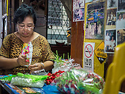 10 SEPTEMBER 2015 - BANGKOK, THAILAND: UMAPOND PONGWIPHANONT, 63, makes flower garlands in front of her home  on Thetsaban Sai 1 Road, a pedestrian footpath next to Wat Kalayanamit. The woman's home, and other homes on the path, are scheduled to be demolished in the next week. Authorities started to destroy 54 homes in front of Wat Kalayanamit, a historic Buddhist temple on the Chao Phraya River in the Thonburi section of Bangkok. Government officials, protected by police, seized the house of Chaiyasit Kittiwanitchapant, a Kanlayanamit community leader, who has led protests against the temple's abbot for trying to evict community members whose houses are located around the temple. Work crews went into Chaiyasit's home and took it apart piece by piece. The abbot of the temple said he was evicting the residents, who have lived on the temple grounds for generations, because their homes are unsafe and because he wants to improve the temple grounds. The evictions are a part of a Bangkok trend, especially along the Chao Phraya River and BTS light rail lines, of low income people being evicted from their long time homes to make way for urban renewal.     PHOTO BY JACK KURTZ