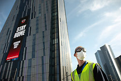 © Licensed to London News Pictures . 21/04/2020. Manchester, UK. An advert telling people to STAY HOME is displayed on the face of the Axis Tower building as cleaners employed to deep clean ambulances that have carried Coronavirus patients are seen wearing PPE as an ambulance arrives for cleaning . The National Health Service has built a 648 bed field hospital for the treatment of Covid-19 patients , at the historical railway station terminus which now forms the main hall of the Manchester Central Convention Centre . The facility is treating patients from across the North West of England , providing them with general medical care and oxygen therapy after discharge from Intensive Care Units . Photo credit : Joel Goodman/LNP