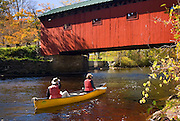 Couple canoeing towards a covered bridge in West Arlington Vermont USA