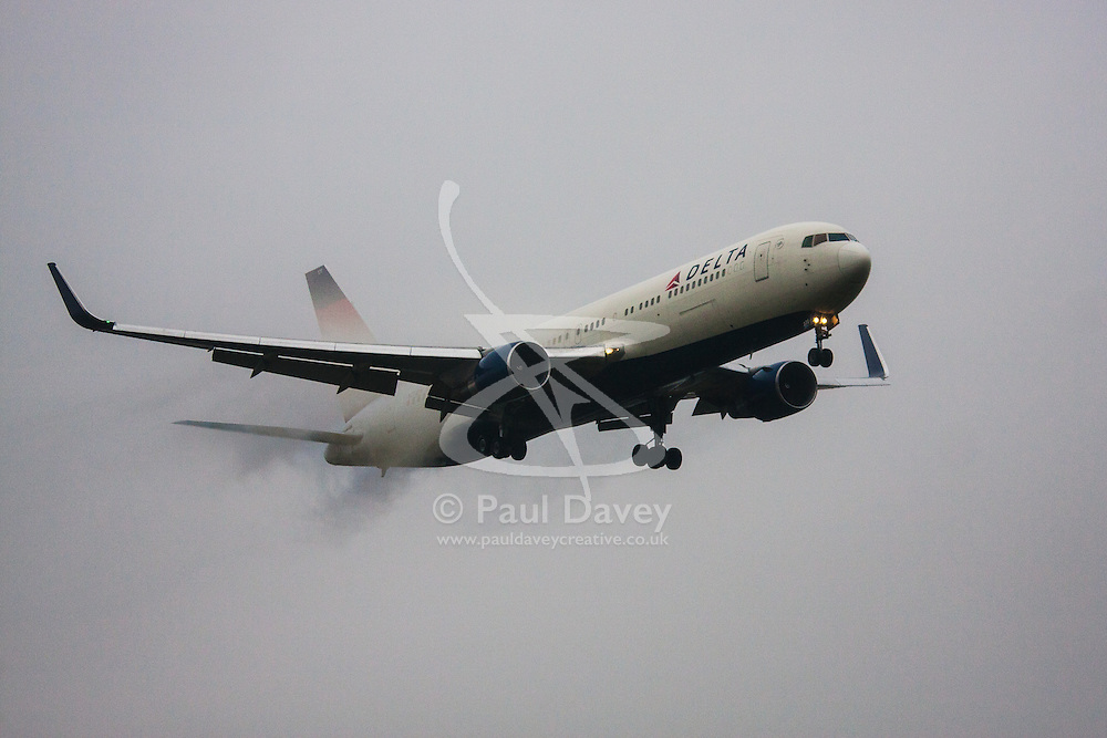 "January 3rd 2015, Heathrow Airport, London. Low cloud and rain provide ideal conditions to observe wake vortexes and ""fluffing"" as moisture condenses over the wings of landing aircraft. With the runway visible only at the last minute, several planes had to perform a ""go-round"", abandoning their first attempts to land. PICTURED: Water vapour streams from the control surfaces of a Delta  Boeing 767 as it prepares to land on Heathrow Airport's runway 27L."