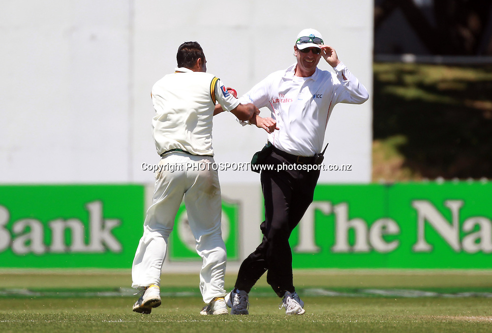 Pakistan bowler Abdur Rehman grabs umpire Rod Tucker as the wind takes hold on Day 2 of the 2nd test match.  New Zealand Black Caps v Pakistan, Test Match Cricket. Basin Reserve, Wellington, New Zealand. Sunday 16 January 2011. Photo: Andrew Cornaga/photosport.co.nz