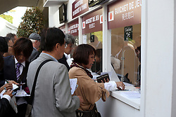 Racing fans from Japan put a bet on  ahead of the Qatar Prix Del'Arc de Triomphe at Longchamp in Paris, France, October 7, 2012. Photo by i-Images.