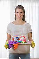 Portrait of smiling woman carrying basket of cleaning supplies at home
