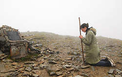 A Pilgrim prays at the summit of Croagh Patrick on reek sunday, over 20,000 made the climb up Ireland Holy mountain in misty and challenging weather ...Pic Conor McKeown
