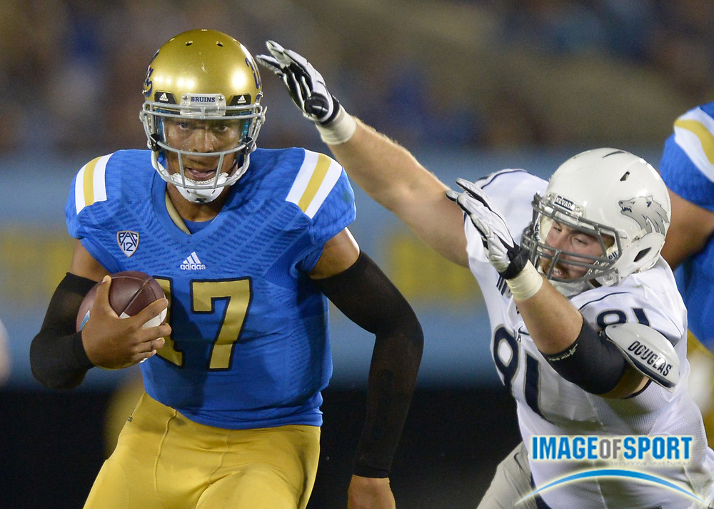 Aug 31, 2013; Pasadena, CA, USA; UCLA Bruins quarterback Brett Hundley (17) is pressured by Nevada Wolf Pack defensive end Jake Peppard (91) at the Rose Bowl. UCLA defeated Nevada 58-20.