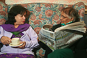 Elderly ladies chatting over a cup of tea and the paper at the Neighbourly Care day centre in Southall.