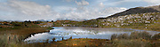 Panoramic view of countryside, Connemara, County Galway, Ireland, in the afternoon, showing a small lake and rocky outcrops in the foreground with distant mountains in the background. The cloudy sky is reflected in the lake. Picture by Manuel Cohen