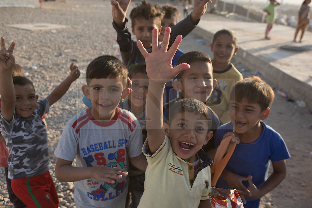Licensed to London News Pictures. 22/10/2016. Young Iraqi refugees wave to the camera at the Dibaga refugee camp near Makhmur, Iraq.<br /> <br /> The crowded Dibaga camp, housing around 28,000 Sunni Arab refugees, is the main gathering point for new IDPs now fleeing areas where ISIS have been pushed out or are in conflict with the Iraqi Army. Photo credit: Matt Cetti-Roberts/LNP