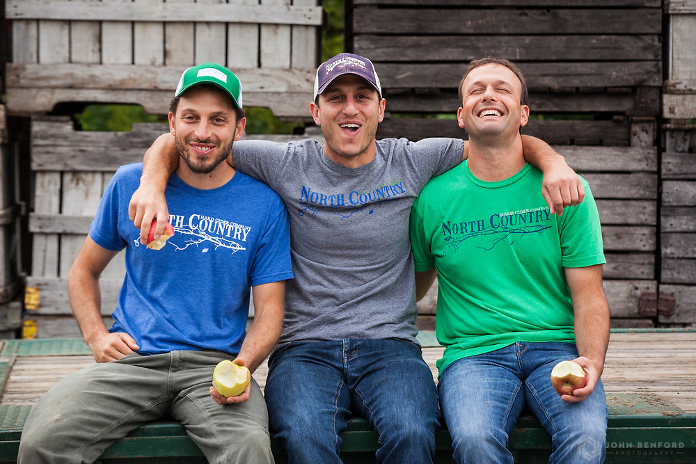 The three cidermakers from North Country Hard Cider enjoy apples and cameraderie while sitting on a flatbed truck in front of large wooden apple crates.