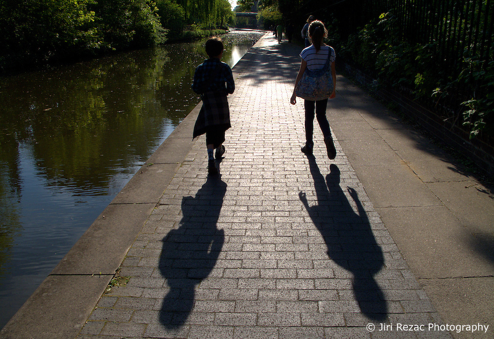 UK ENGLAND LONDON APR11 -  Silhouette of two children walking along the Grand Union Canal in London. The Grand Union Canal in England is part of the British canal system. Its main line connects London and Birmingham, stretching for 137 miles (220 km) with 166 locks...jre/Photo by Jiri Rezac..© Jiri Rezac 2011