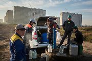 People collect water from a pump beside a new residential development in Astana, Kazakhstan. Despite the pace of development in the city many older homes do not have running water and so residents have to collect their supply from pumps that are dotted around the city.