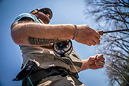 A man with a grouse feather tattoo on his forearm flyfishing the Grand River near Grand Rapids, Michigan.