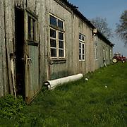 Nederland - Veendam - ( Groningen ) - 14-04-2009<br />De ' Veendammer Barak'  in het Lanschap bij Veendam, deze barak stond op Kamp Westerbork en deed dienst batterijensloperij.<br /><br />Barak 57<br /><br />Barak 57 was gebouwd om dienst te doen als werkbarak. In 1943 werd deze een tijd als woonbarak gebruikt. Mensen die direct op transport moesten, werden onder meer hierin ondergebracht. Eind augustus 1943 werd de &lsquo;57&rsquo; weer industriebarak. Hierin was de batterijsloperij gevestigd. Van dit smerige en ongezonde werk zijn in het voorjaar van 1944 filmopnamen gemaakt, die bewaard zijn gebleven. <br />Anne Frank en haar zusje Margot hebben een aantal weken in deze barak moeten werken.<br /><br />Evenals de rest van het kamp bleef deze barak na de bevrijding in gebruik. In 1957 werd nr. 57 verkocht om een nieuwe bestemming in Veendam te krijgen. De oorspronkelijk 84 m lange barak werd in tweeën gedeeld en de beide delen werden naast elkaar geplaatst. Aldus was het object geschikt als landbouwschuur, tot op heden.<br />Binnenkort zal deze &lsquo;Veendammer&rsquo; barak worden gedemonteerd en naar het Herinneringscentrum worden overgebracht om te worden geconserveerd. Gedacht wordt om deze bijna zeventig jaar oude &lsquo;57&rsquo; weer een plek op de oorspronkelijke plaats te geven.<br /><br />In de op Harry Mulisch&rsquo; boek gebaseerde film &lsquo;The discovery of heaven&rsquo; figureert deze barak. &nbsp;<br />Foto: Sake Elzinga