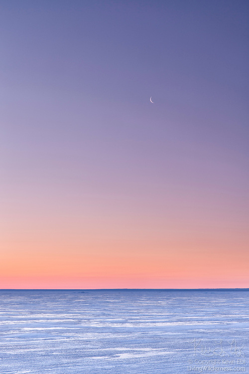 The crescent moon is visible above the frozen surface of Lake Michigan just before sunrise over Tahquamenon Bay in Michigan's Upper Peninsula.