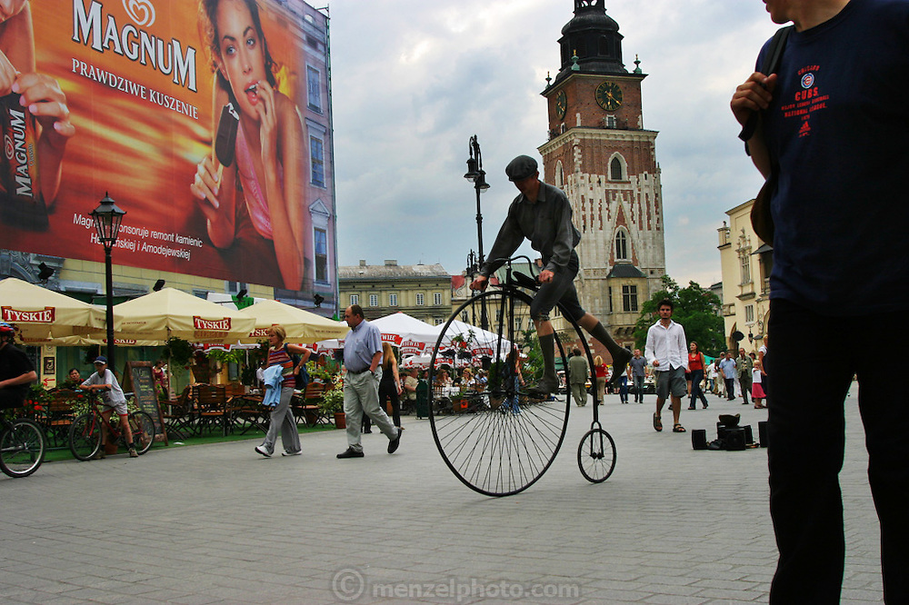 Krakow, Poland summer in Rynek Glowny (old town square) with man mounting an old bicycle and Magnum ice cream billboards.