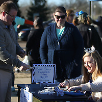 Miss Riverland Haley Jones sells a Blue Star of Hope Pin to Mayor Shelton Saturday during the Run for Your Buns 5k at Fairpark