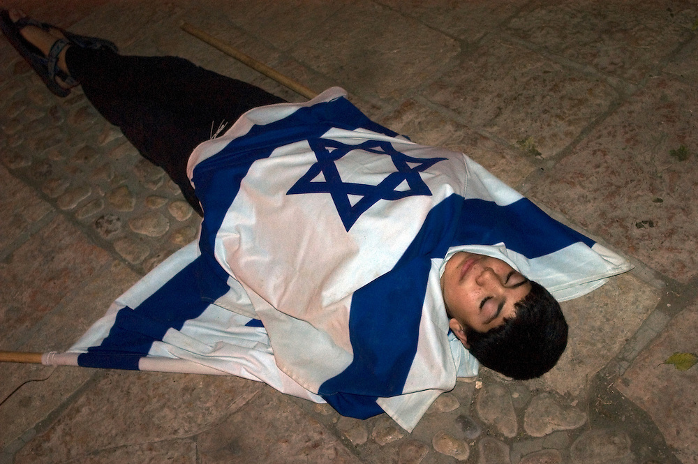 A young boy rests under an Israeli flag during rehearsals for a youth show in Hebron's Jewish community. Some six hundred Jews live in the heart of the old city surrounded by over 160,000 Palestinian inhabitants..Hebron, Israel. 04/11/207.Photo © J.B. Russell/Blue Press