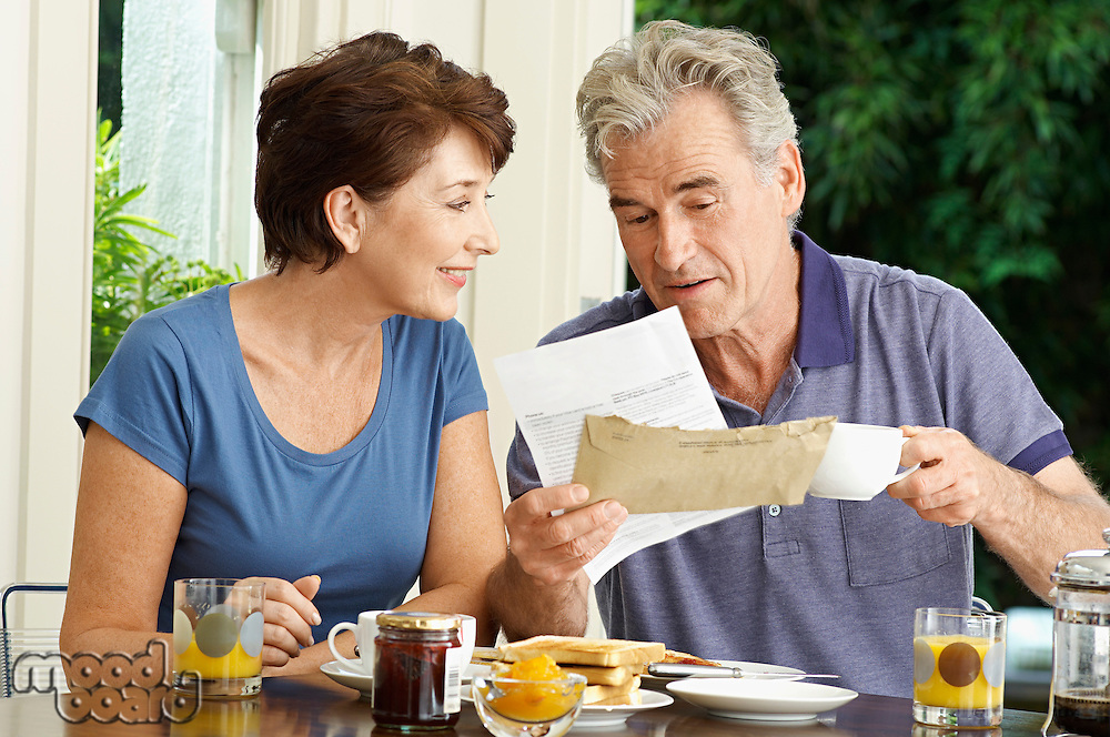 Middle-aged couple looking at bill over breakfast