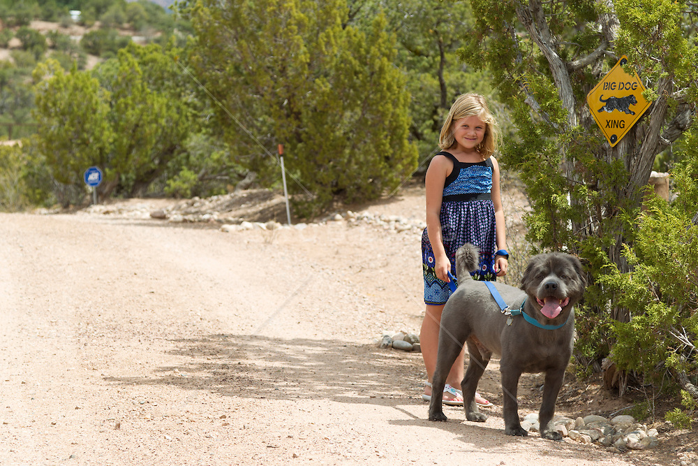 small girl walking with a big dog my a big dog crossing sign in New Mexico