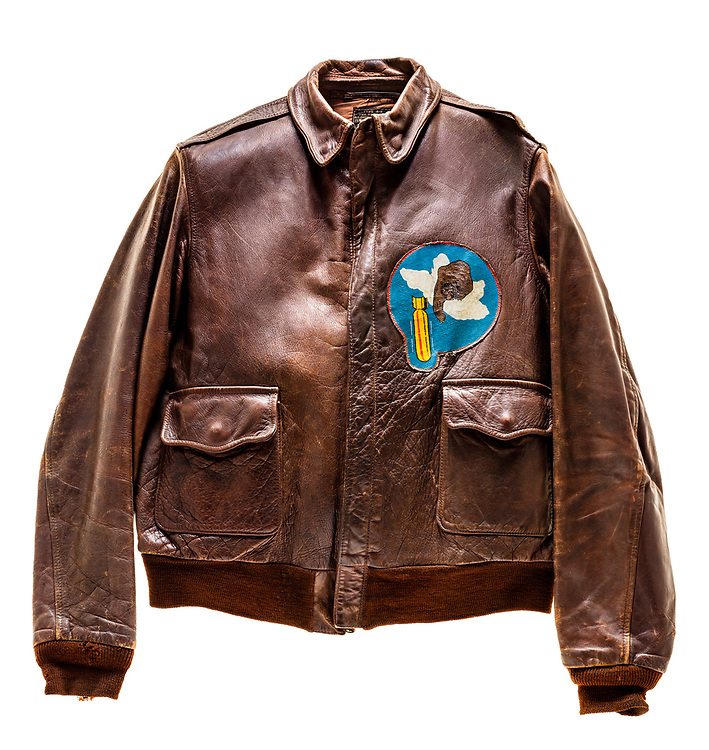"""This type A2 flight jacket was worn by John G. Stanley, a tail gunner on the """"Diplomat"""". The 569th squadron patch is attached to the front of the jacket, and the name """"Diplomat"""" above a swastika and a B-17 is painted on the back. Each bomb painted on the jacket signifies a successful mission. The """"Diplomat"""" was WIA (wounded in action) while flying a mission on December 24, 1944, and was declared salvage on February 6, 1945."""