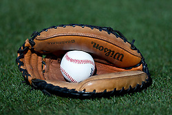 OAKLAND, CA - AUGUST 20: Detailed view of a Wilson catcher's glove with a baseball on the field before the game between the Oakland Athletics and the Seattle Mariners at O.co Coliseum on August 20, 2013 in Oakland, California. The Seattle Mariners defeated the Oakland Athletics 7-4. (Photo by Jason O. Watson/Getty Images) *** Local Caption ***