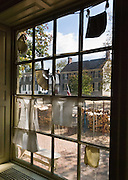 "The window of a Milliner & Tailor shop looks out onto Duke of Gloucester Street at Colonial Williamsburg. Colonial Williamsburg is the historic district of the independent city of Williamsburg, Virginia, which was colonial Virginia's capital from 1699 to 1780, and a center of education and culture. The capital straddled the boundary of two of the original shires of Virginia, James City Shire (now James City County), and Charles River Shire (now York County). Here, Thomas Jefferson, Patrick Henry, James Monroe, James Madison, George Wythe, Peyton Randolph, and dozens more helped mold democracy in the Commonwealth of Virginia and the United States. Motto: ""that the future may learn from the past.""  The Historic Area exhibits colonial houses and American Revolutionary War history. Prominent buildings in Colonial Williamsburg include the Raleigh Tavern, the Capitol, The Governor's Palace, and Bruton Parish Church. Interpreters work, dress, and talk as they did in the era, teaching visitors. The 301-acre Historic Area is located immediately east of the College of William and Mary, which was founded at Middle Plantation in 1693. The new College, long a desire of the colonists, was a key factor in the establishment of the town as capital of Virginia in 1698 and its renaming for King William III of England shortly thereafter.  Jamestown and Yorktown, the other two points of the Historic Triangle, are linked to Colonial Williamsburg by the National Park Service's bucolic Colonial Parkway."