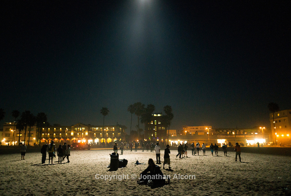 An LAPD helicopter spotlight falls on the last remaining people at the Venice Beach drum circle. Recent Venice Beach drum circles were closed down because they were violating beach rules and disturbing some Venice residents.