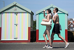 © Licensed to London News Pictures. 03/07/2018. Hove, UK. A young couple in beach attire walk past colourful beach huts on the seafront at Hove, East Sussex on the south coast of England, as a heatwave continues across the UK. Photo credit: Ben Cawthra/LNP