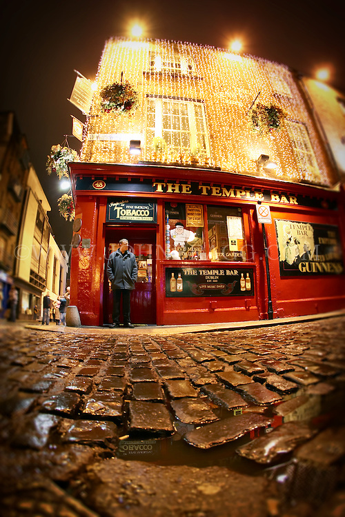 A man standing in the doorway of The Temple Bar in Dublin, Ireland