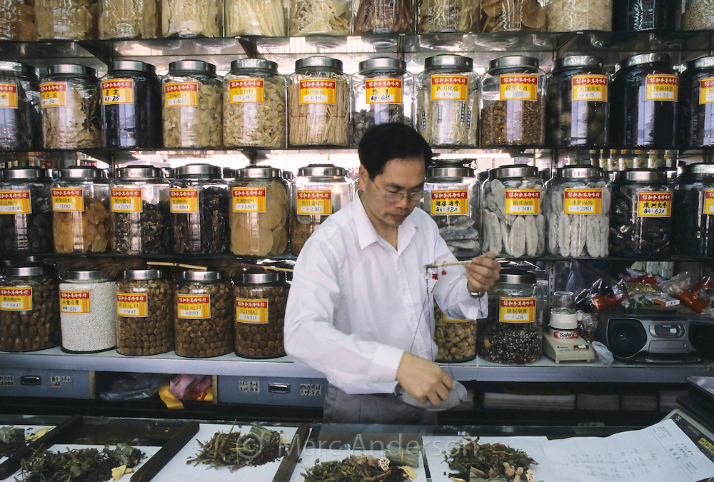 A man weighing dried ingredients for Chinese medicine in a tradiotnal shop, Hong Kong, China.