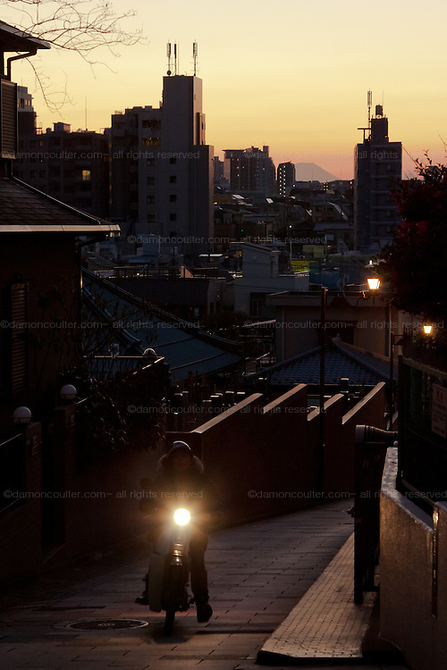 A moped climbs the street during sunset over Fujimazaka (Mount Fuji viewing Hill) in Nishi Nippori, Tokyo, Japan. Friday January 11th 2013. This is the last street level place in central Tokyo to see Mount Fuji and is threaten with development that will block the view of this iconic peak.