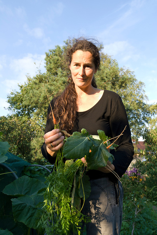 Eine Frau im Alter von Mitte vierzig Jahren steht in einem privaten Garten und zeigt mit  Bedauern eine winzige Möhre|  A woman at the age of 45 stands in her garden with some fresh harvested vegetable and is showing a very thin carrot