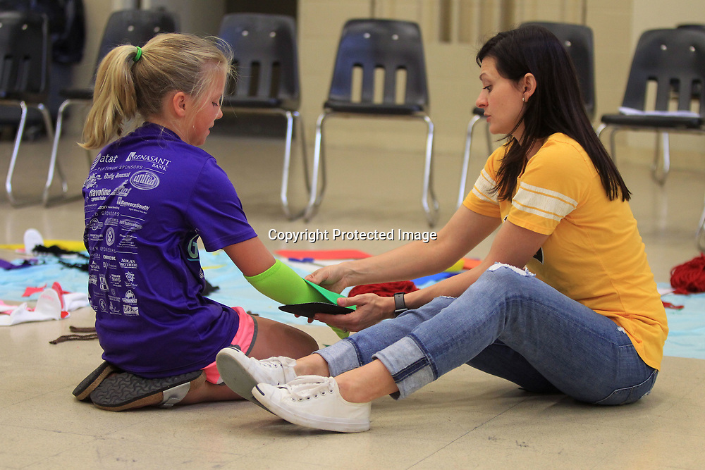 Catherine Long, 9, of Tupelo, is helped by Amy Fagan, an instructor at the Pied Piper Theater Camp, with the sock puppet that Long is making into a turtle during crafts time Wednesday morning.