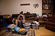 "Lauren Burnett folds laundry for the family at their home in New Franklin, Mo. Since her mother's illness has progressed Lauren picks up additional chores around the house. ""Poor little Lauren I told her you're going to have to step up to the plate because I don't know what's going to happen and she did. She just does an amazing job. She worked and she took on a big responsibility and I knew at that point she's going to be ok if something does happen,"" Burnett said."