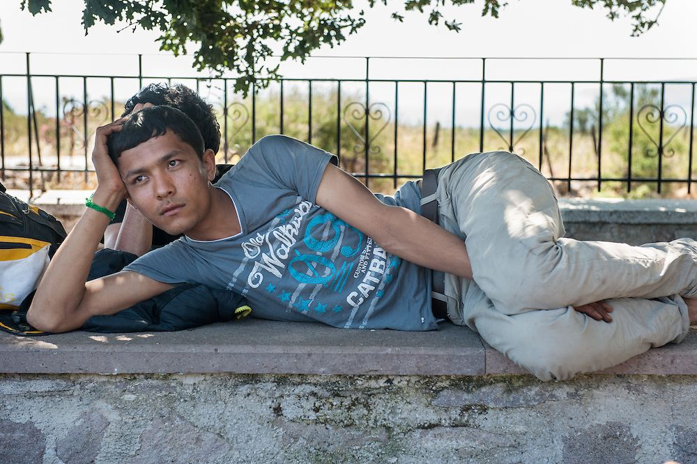 Kadir from Afghanistan resting in a church yard near the village of Mantamados. Refugees land at the northern shores of the island of Lesbos and then they have to walk the 9 hour distance to one of the camps.
