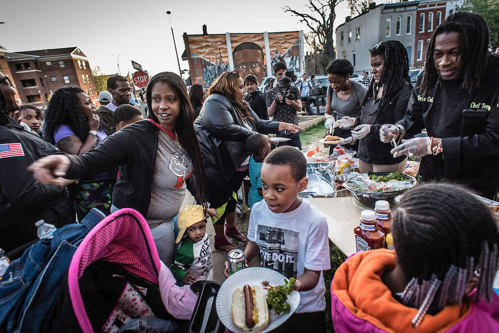 BALTIMORE, MD -- 4/19/16 -- On the anniversary of Freddie Gray's death, residents, activists, and the media gathered at Presbury and Mount Streets in Sandtown to mark the date. The activist group Leaders of a Beautiful Struggle held a cookout and gave away free food within sight of the spot where Freddie Gray was arrested.  Safe Streets is a program started in Baltimore to cut gun violence in the most dangerous communities in the city by deploying Violence Interruptors to deescalate conflicts before they turn deadly. The newest post has just opened in the long beleaguered Sandtown community which was ground zero for the city's unrest following the death of Freddie Gray…. (photo by Andre Chung for The Washington Post)