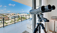 View of a window of a luxury apartment with binoculars. View of Miami Beach.