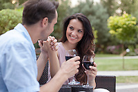 Romantic young couple having red wine in park